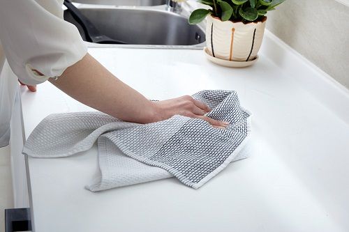 Woman Cleaning Kitchen Counter with Kitchen Towel