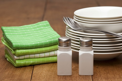 Green Dish Towels on Table Next to Kitchen Utensils